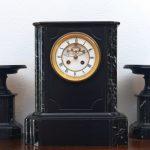 Großaufnahme der gesamten Marmoruhr. Neben der Uhr sind auch zwei passende Kerzenständer zu sehen.