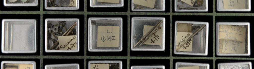 Detailaufnahme von Uhrenteilen in kleinen durchsichtigen Boxen