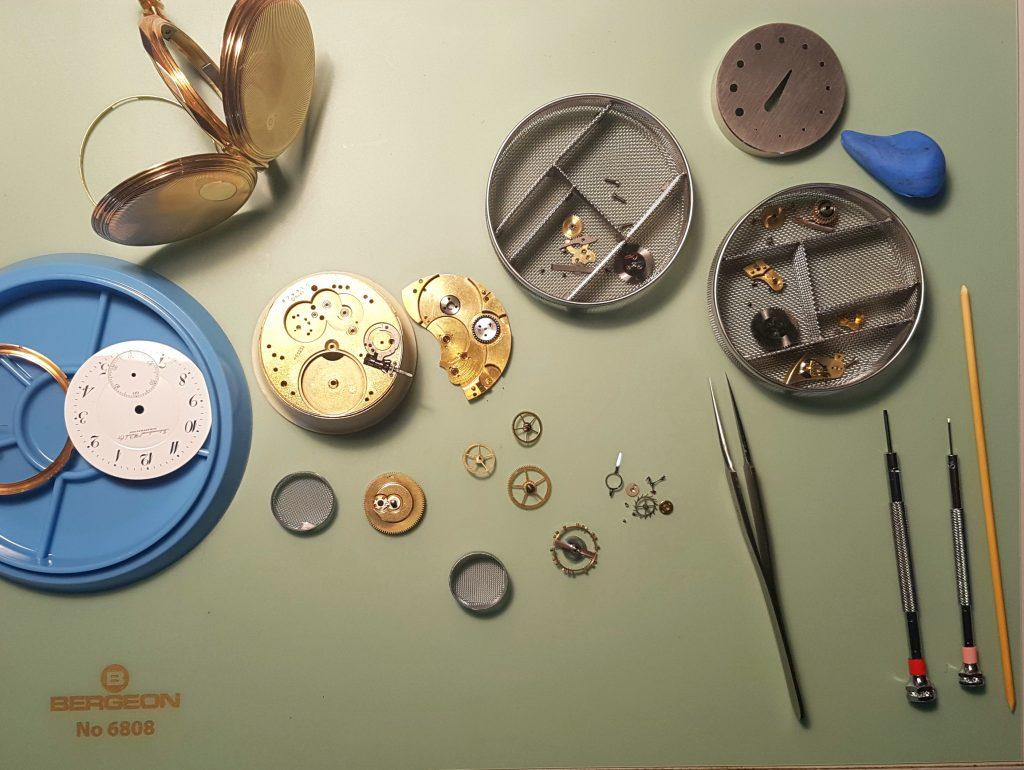 Uhrmacherhandwerk. Zerlegte Uhrenteile eienr IWC Taschenuhr am Uhrmacher Tisch. Pinzette. Schraubenzieher, Reinigungskörbchen.